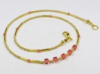 goldfarbenes Collier mit glitzernden roten Würfeln