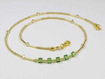 goldfarbenes Collier mit glitzernden grünen Würfeln