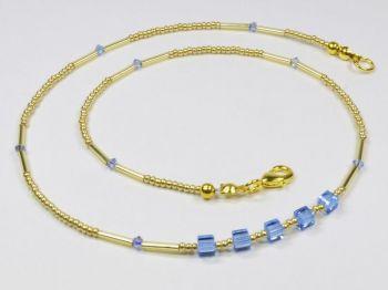 goldfarbenes Collier mit glitzernden blauen Würfeln