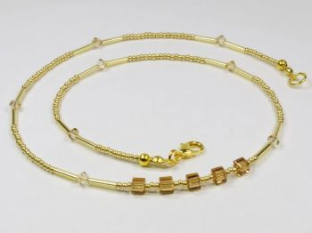 goldfarbenes Collier mit glitzernden braunen Würfeln